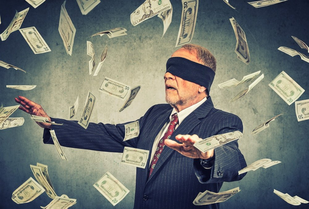 Blindfolded senior businessman trying to catch dollar bills banknotes flying in the air on gray wall background. Financial corporate success or crisis challenge concept